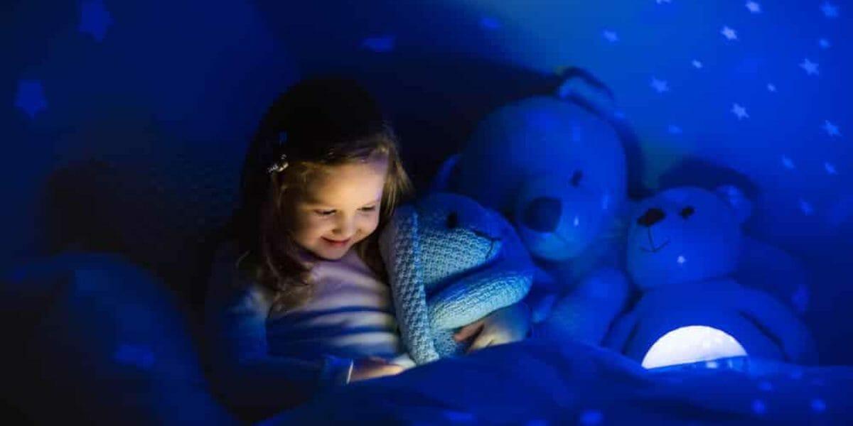 fille dans son lit éclairée par une veilleuse enfant