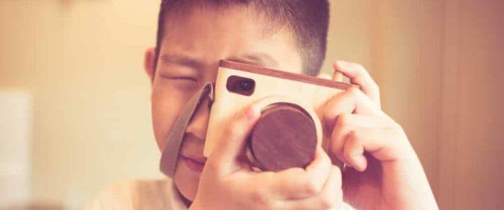 enfant qui prend une photo avec son appareil photo numérique