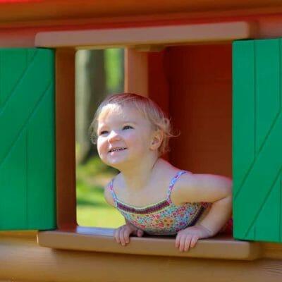 petite fille à la fenêtre de sa cabane de jardin en plastique pour enfant