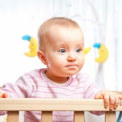 bébé dans un parc bébé en bois