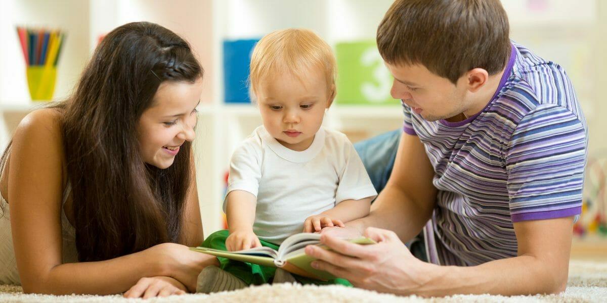 parents avec leur bébé lisant un livre à toucher