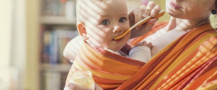 bébé dans une écharpe meï-taï sur le ventre de sa mère