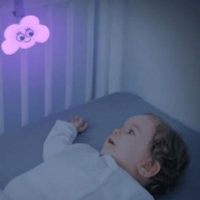 veilleuse nuage accroché barreaux lit bébé. bébé allongé dans le lit et regarde la veilleuse nuage