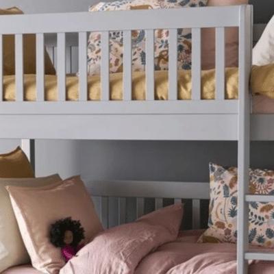 lit superposé blanc avec des couettes, des coussins et des peluches