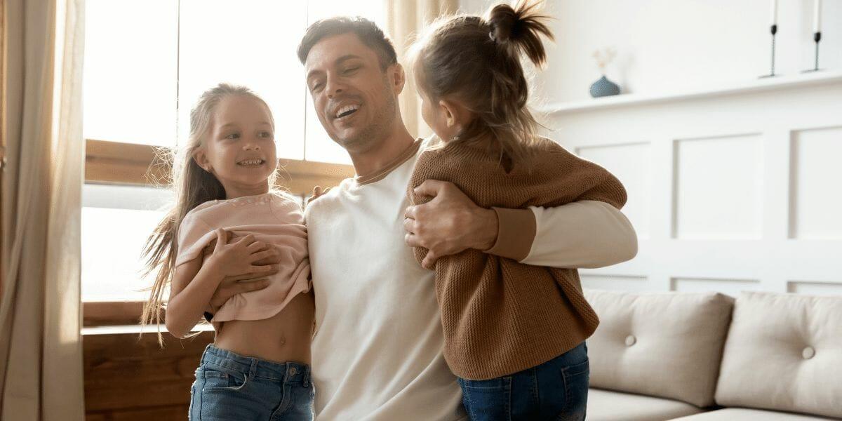 deux petites filles dans les bras de leur papa