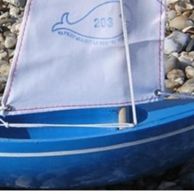 bateau bleu avec voile blanche marque Tirot