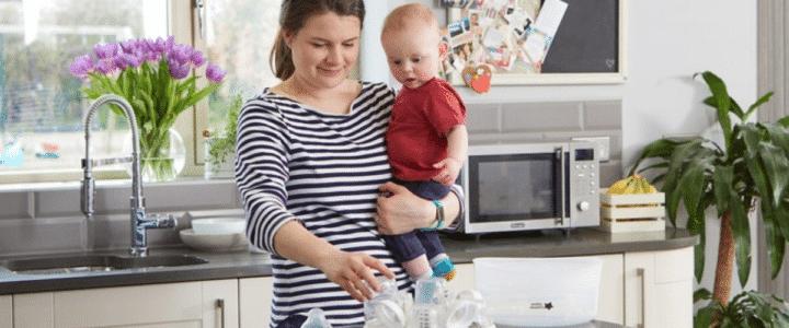 Maman avec un bébé dans les bras devant un sterelisateur