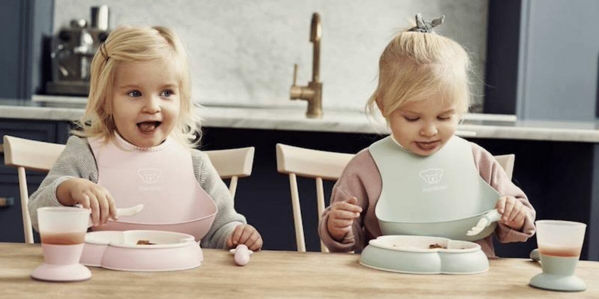 deux enfants à table avec bavoirs