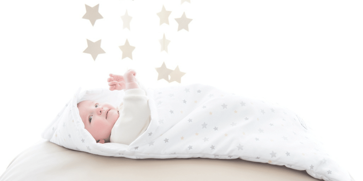 bébé dans un nid d'ange avec étoile au dessus de sa tête